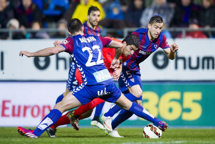 Luis Suarez of FC Barcelona duels for the ball with Raul Rodriguez Navas of SD Eibar during the La Liga match between SD Eibar and FC Barcelona at Ipurua Municipal Stadium on March 14, 2015 in Eibar, Spain.