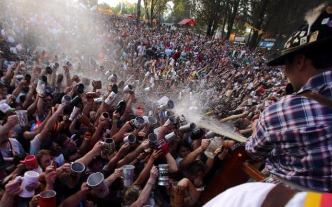 Visitors try to fill their mugs as beer is sprayed on them from a barrel at Argentina's Oktoberfest, the national beer festival, in Villa General Belgrano, Argentina