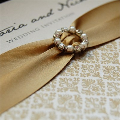 Wedding invite with gold ribbon and antique style brooch