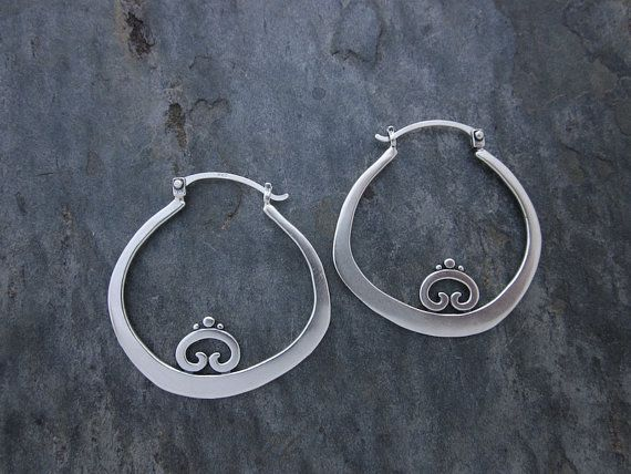 A single decorative swirl motif adorns these elegant thick hammered hoops  for a look that is feminine and tribal. Created to be lightweight, these  are super comfortable to wear with an easy to use 'v clasp' ear wire that's  both safe and functional.   As shown, they measure 1.5 inches top to bottom for the perfect mid-large  sized earring. Sturdy yet not heavy on the lobe, created entirely from  sterling silver in our Los Angeles studio.  All plated items are finished over sterling silver…