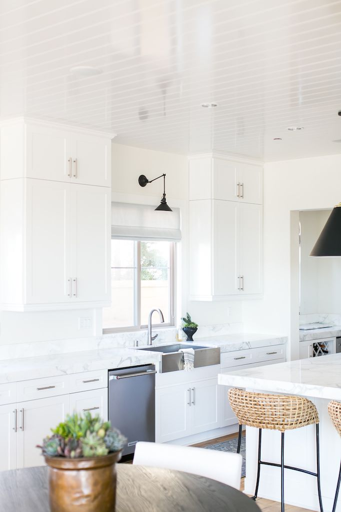 BECKI OWENS- Estillo Project: Classic Modern Kitchen. A white kitchen  with statuary marble, Benjamin Moore Swiss Coffee paint, black cone pendants, Rejuvenation swing arm sconce, and stainless steel apron sink.