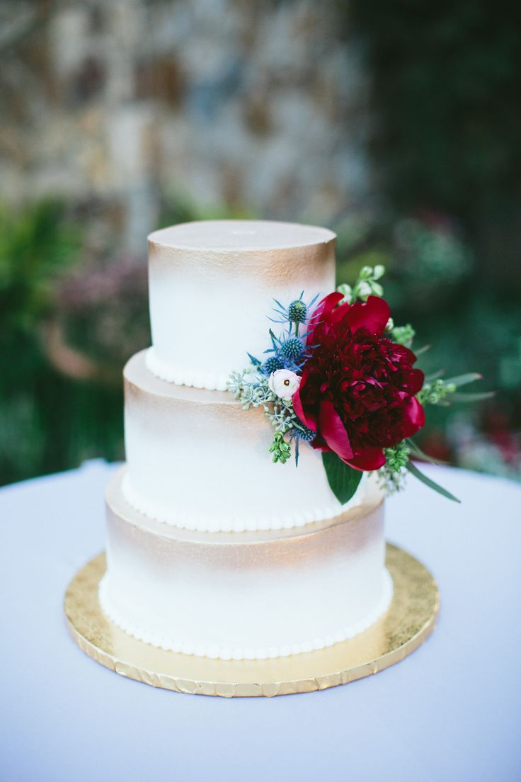 a single cluster of gorgeous red charm peony, blue thistle, pink ranunculus and larkspur buds and bits of greenery makes a statement on this sweet wedding cake highlighted with gold.