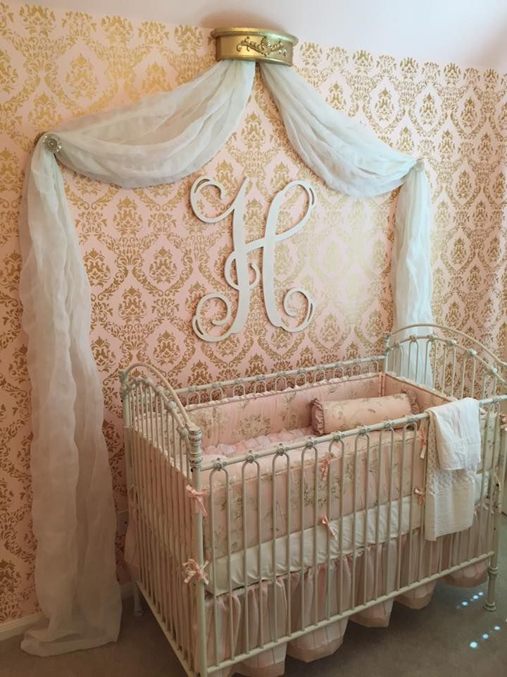 Peachy pink and gold nursery accent wall with monogram and gold foil damask…