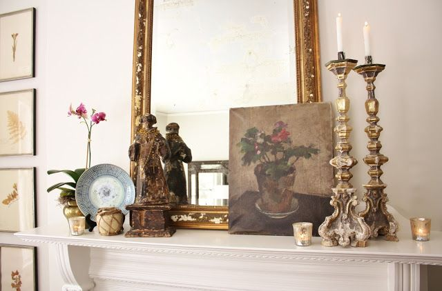 The antique French gilt mirror is a staple on the living room mantel and it shares the stage with a pair of 17th century gilt and gesso church alter candlesticks that we found at the Paris flea market, along with a favorite oil painting (circa 1922), an antique Santos, an antique Chinese wicker-wrapped earthenware ginger jar, an antique Chinese blue and white dish and an orchid in an antique Russian brass jardiniere along with a trio of mercury glass candle holders from Pottery Barn.