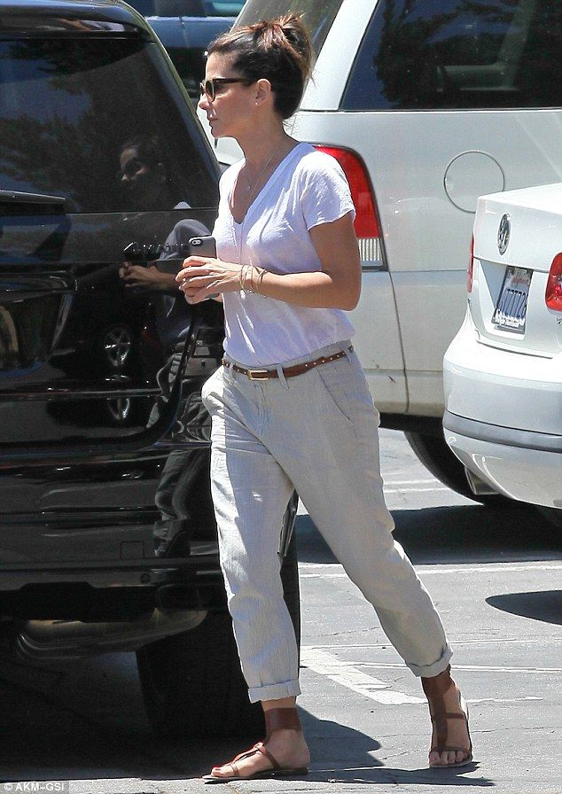 Always stylish: The 48-year-old was dressed-down chic in khaki trousers paired with a white T-shirt and brown leather sandals