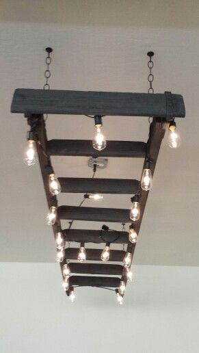 $30 LADDER CHANDELIER project! Used an old junk ladder, Edison bulb string lights, and some flat grey and flat black paint to dry brush. Turned out amazing!!