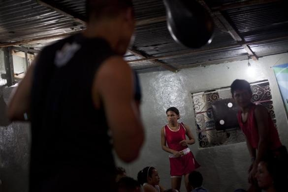 Elizabeth Palencia, 20, takes a break during a training session of Olympics-style street boxing at a gym in the low-income neighborhood of La Vega in Caracas February 10, 2011.  REUTERS/Carlos Garcia Rawlins