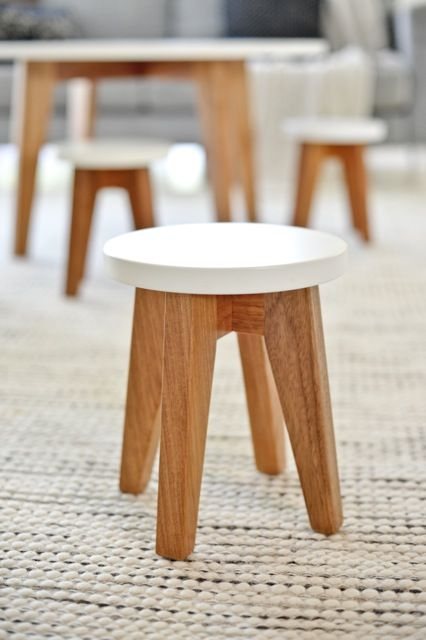 The legs have wood color, while the top is painted white. It's a simple design and looks apt for kindergarten.