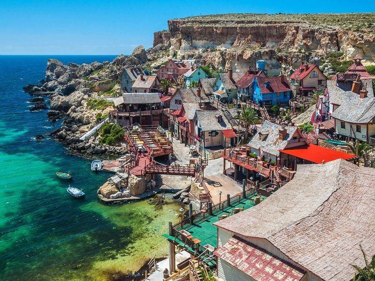 """A aldeia de Popeye em Malta foi construída para o filme """"Popeye"""" (1980) e depois foi transformada num parque de diversões. Os troncos de árvores utilizados para a construção das casas foram importados da Holanda. Também foram utilizados cerca de 7.500 litros de tinta. Os turistas podem aproveitar para fazer uma viagem de barco, visitar uma adega ou saltar num trampolim na água.  Leia mais no https://insider.pro/pt/article/73323/"""