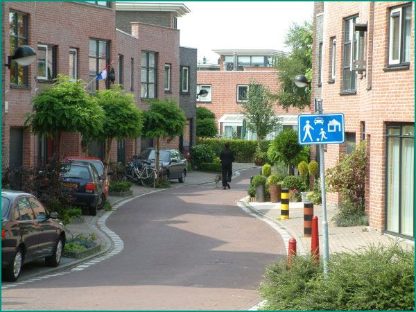 Woonerfs. Used to de-emphasize cars and place the importance on pedestrians. Also sustainable by having trees and vegetation to manage storm water runoff.