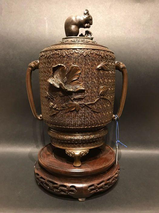 Overdekte pot in brons - Japan - begin van de 20e eeuw  Zittend op drie kleine voeten de cilindrische buikje versierd met een reliëf van bloemen vogels en insecten op een achtergrond van geometrische patronen de lange handgrepen gemonteerd met dierlijke hoofden de dekking uitgebreid met een rat-figuur die fungeert als de stekker; de pot is opnieuw gelakt en de staart van de rat hersteld.H: 28 cmBron van de veiling ARTCURIAL een Parijs  EUR 500.00  Meer informatie
