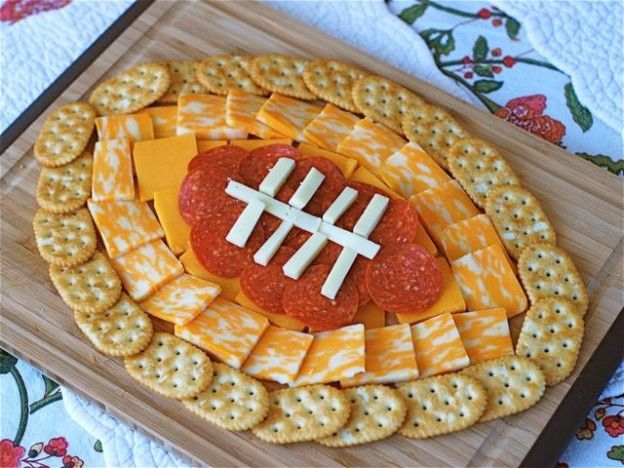 Football-Cheese-Plate ~ When you have this snack at your tailgating party, make it a little more festive by designing it as a football! Using the crackers, cheese, and pepperoni, you can make a football design that will go right along with your other decorations! For some calorie savers, use turkey pepperoni and reduced fat cheese slices.  Suggestion only.