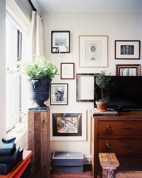 gallery wall of art surrounding a wooden chest topped with a TV
