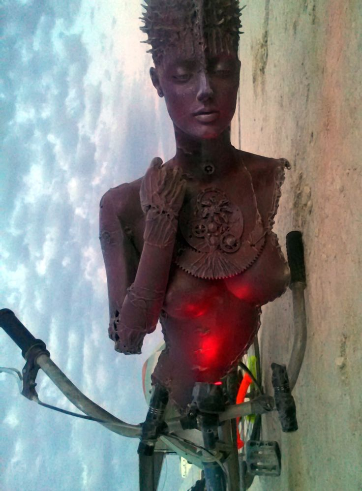 Piranha Girl attached to Bendy Bike at Burning Man. Basically a swing bike with huge hood ornament!