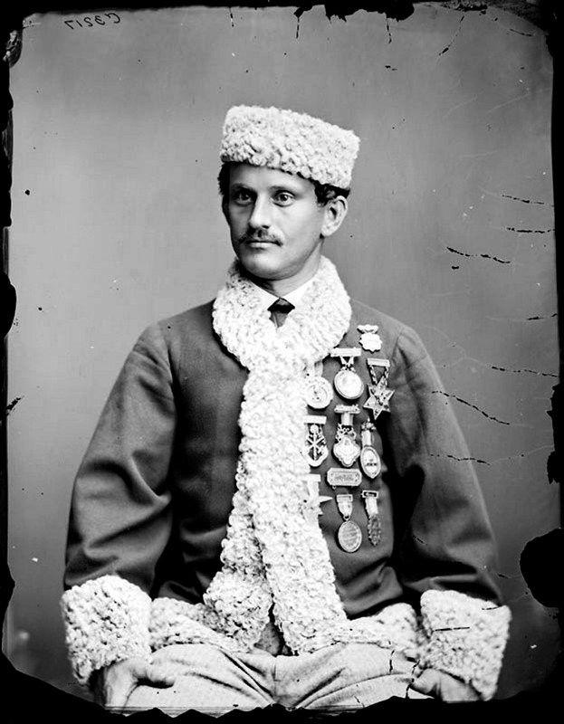 Stockholms digitala stadsmuseum — Porträtt i halvfigur av skridskokungen Jackson Haines iförd pälsmössa och pälsbrämad jacka med medaljer på bröstet.