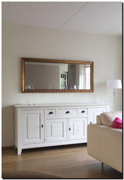 Mooie klassieke spiegel met gouden lijst boven het dressoir