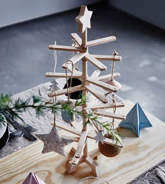 A decorative wooden Christmas tree sits on a dining table.