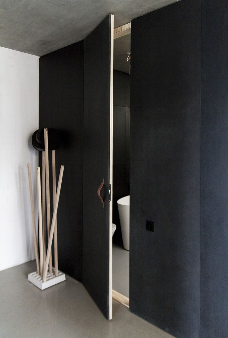 mieszkanie własne w Gdyni - PRACOWNIA 111  Full-height bathroom door covered in raw pine veneer inside and olied black MDF outside. Bathroom is a black capsule stuck between to concrete surfaces.