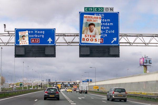 Misschien heeft u ze al zien hangen: de enorme verkiezingsposters van BOOS! De politieke partij liet de posters dit weekend plakken op talloze verkeersborden boven de snelweg. Rijkswaterstaat eist dat de de posters onmiddellijk worden verwijderd. De posters hangen onder meer boven de A12 bij Den Haag en langs de A1 bij Apeldoorn,kennelijk ter promotie van de verboden politieke partij. [...]