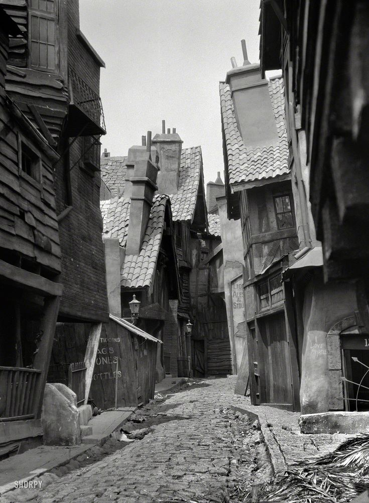 "Circa 1920. ""Unidentified buildings, possibly movie set, associated with Famous Players-Lasky."" This seriously askew alleyway has a Dickensian-Disneyesque vibe"