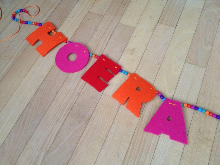 """Verjaardagsslinger van vilt en kralen: letters printen en uitknippen, in spiegelbeeld omtrekken op vilt en uitknippen, met nagelschaartje oid twee gaatjes per letter prikken (zodat de letters niet schuin gaan hangen) en rijgen maar met kralen ertussen! Tip: maak een knoopje tussen """"hoera"""" en de naam en tussen de naam en """"jarig"""". Zo kun je er gemakkelijk een andere naam tussen hangen en is de slinger vaker bruikbaar!"""