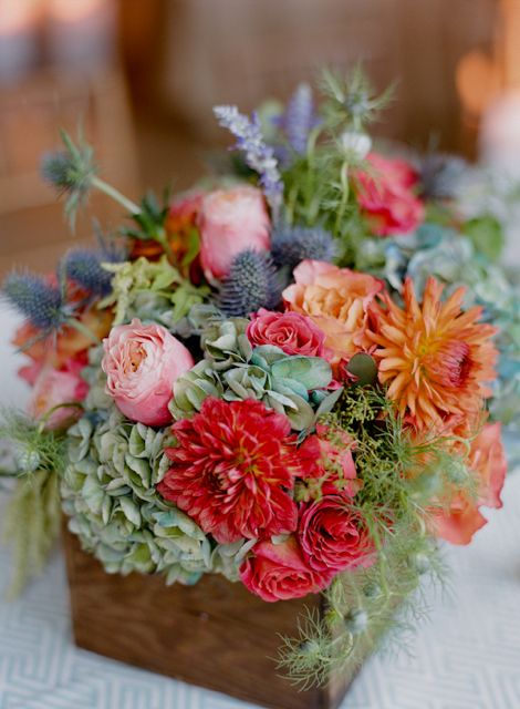 Free spirit roses, were paired with blue hydrangea, blue thistle, spray roses, herbs, dahlias, and nigella.