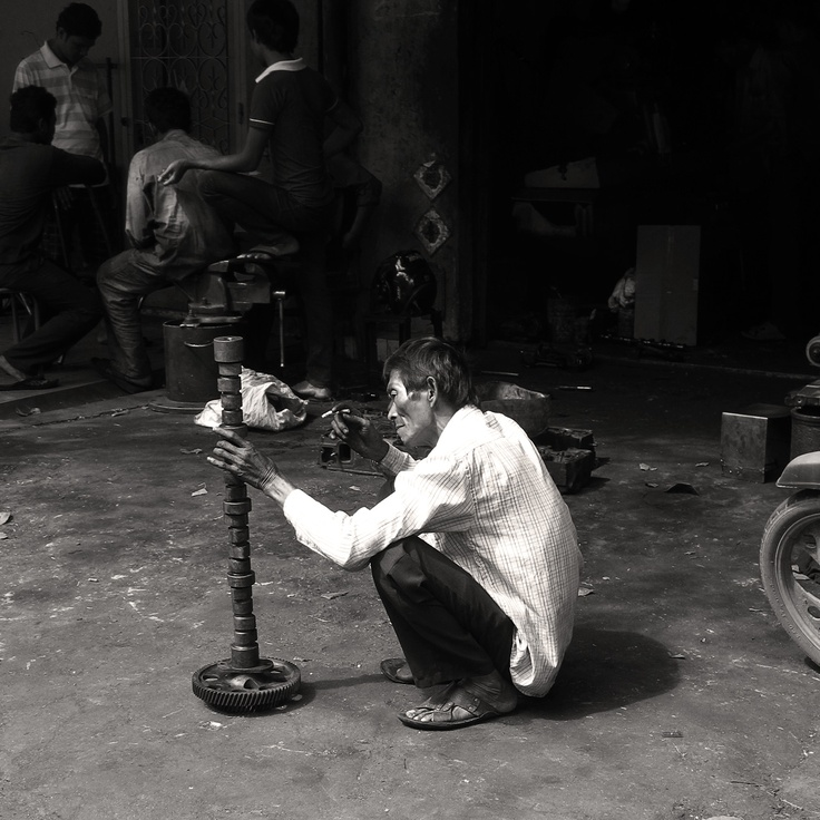 Street Photography: Metal Workshop    My non-engineering mind is puzzled as to what he is doing. It looks as though he is performing a detailed inspection, but he could simply be just having some fun creating a tall stack.    Website: www.tropicalasiatravel.com