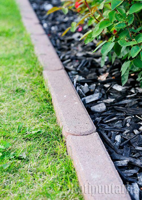 Betoninen reunakivi upotettuna istutusalueen ja nurmikon väliin.
