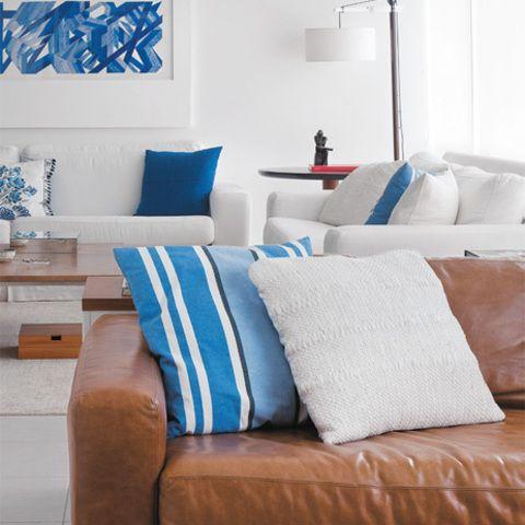 As cores dominantes da sala são o azul e o branco. O sofá em L de couro caramelo é de Paulinho Estofador e almofadas, do Empório Beraldin.