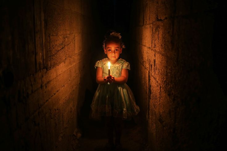 A Palestinian girl holds a candle to light her home after a power cut at the Jabalia Camp in Gaza City, Gaza Strip on June 27. Two-million people living in Gaza are suffering power outages as the Israeli siege there continues.