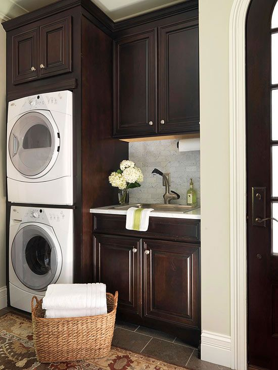 I like this laundry room! the sink is conveniently located next to the stacked washer and dryer. and, of course, i love the dark wood. (kv)