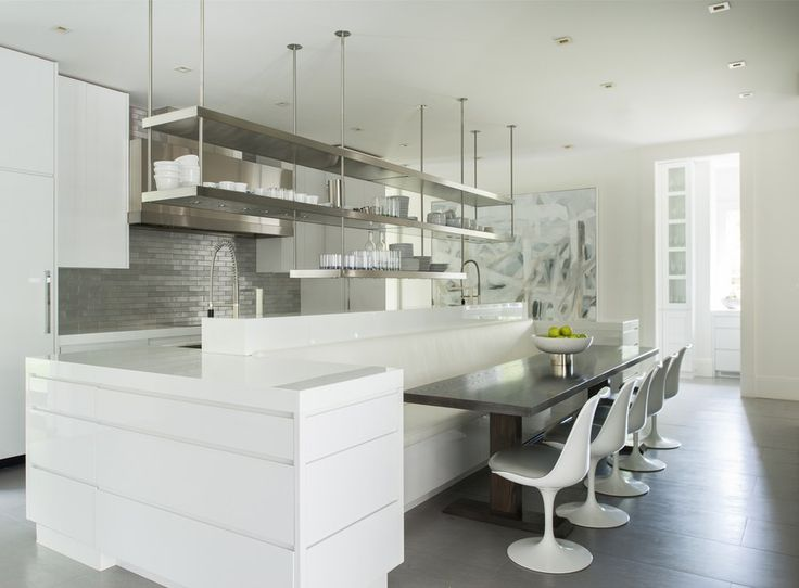 """""""She's in the kitchen often,"""" says Brooks of the homeowner. """"That's what precipitated the large, 16-foot island."""" The wife also values organization, which propelled Brooks to choose clean, glossy white cabinetry with no hardware. Above the island hangs a diner-style stainless-steel plate rack. In lieu of barstools, the design team incorporated a roomy custom banquette paired with Design Within Reach's Saarinen Tulip chairs in a hard-wearing faux white leather; an abstract art piece by Shauna…"""