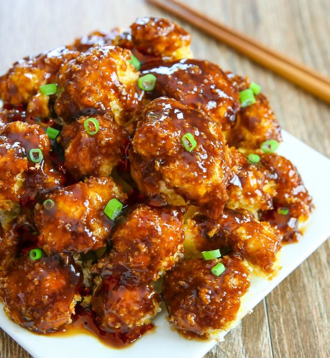 Crispy baked cauliflower pieces are coated in an orange sauce. It's ...