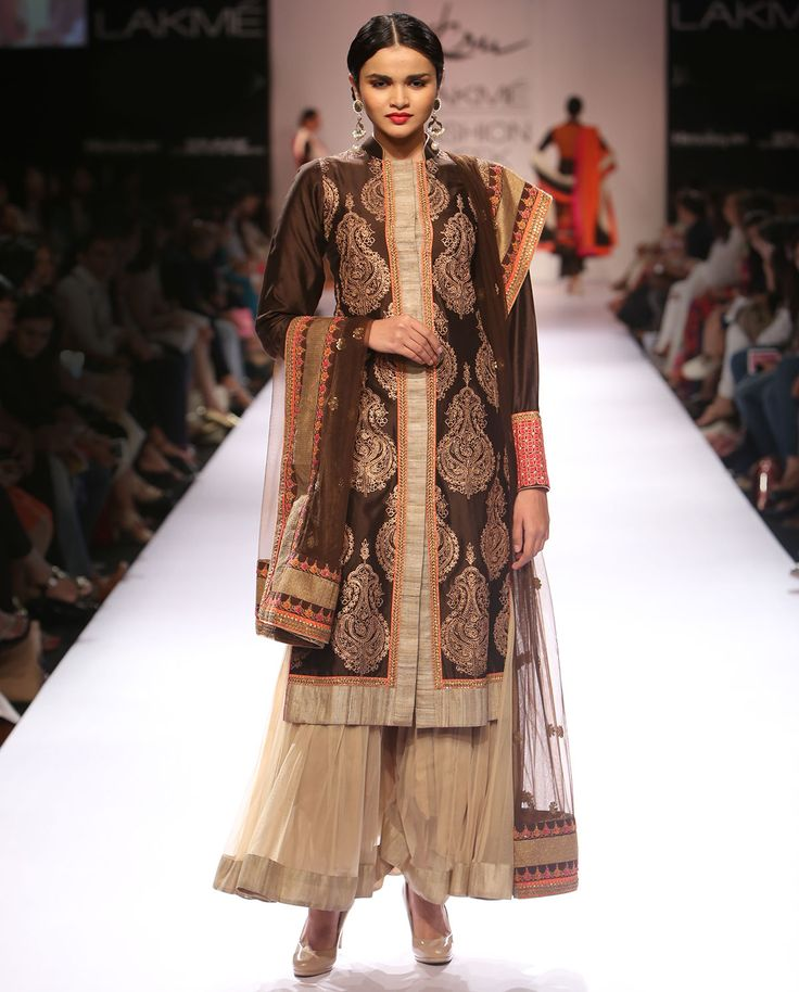 Bistre brown suit with golden embroidery details all across. Beige gold panel across the placket and hem. Contrasting red tinted embroidered cuffs. Contrasting bright dupatta with similar detailing. Matching beige toned sharara.