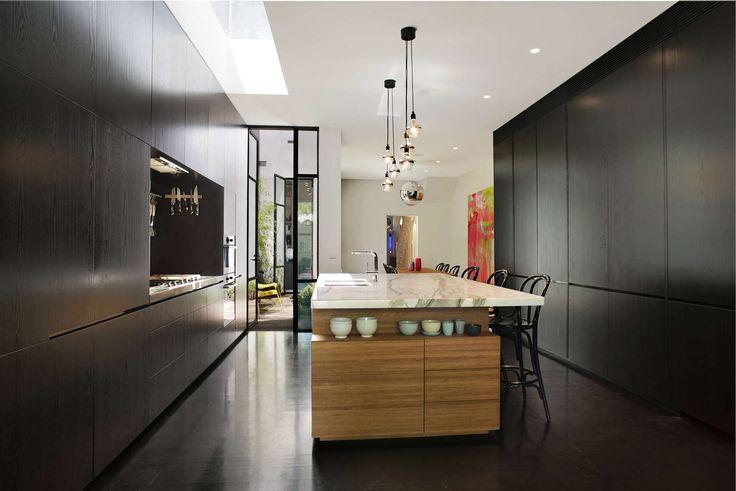 Cucina moderna con massicci mobili di colore nero, isola in legno con piano in marmo e pavimenti in cemento effetto lucido