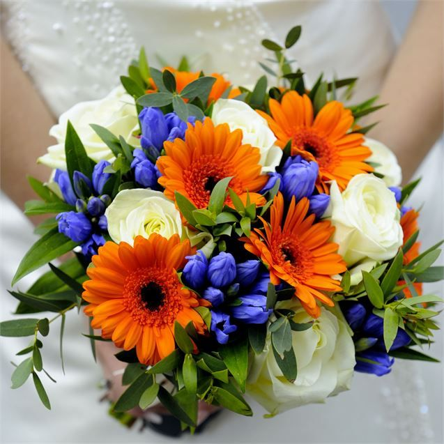 Ebenezers in Shropshire helped Gemma and Adam choose their wedding flowers. Gemma carried a gorgeous bouquet down the aisle which incorporated orange, ivory and blue flowers to match the colours of the bridesmaids dresses and groomswear accessories.  Each bridesmaid carried a smaller bunch of hand-tied gerberas and the grooms party each wore a single gerbera button hole.To decorate the reception tables Gemma arranged for tall white vases to be filled with blue flowers which not only looked…