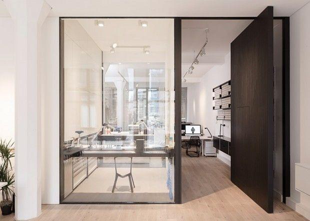 les bureaux londoniens de la marque horlogère Uniform Wares conçus par Feilden Fowles. À côté de la grande fenêtre vitrée, une séparation en bois sombre de même taille s'ouvre et se ferme pour permettre l'accès au studio de conception qui se trouve derrière.