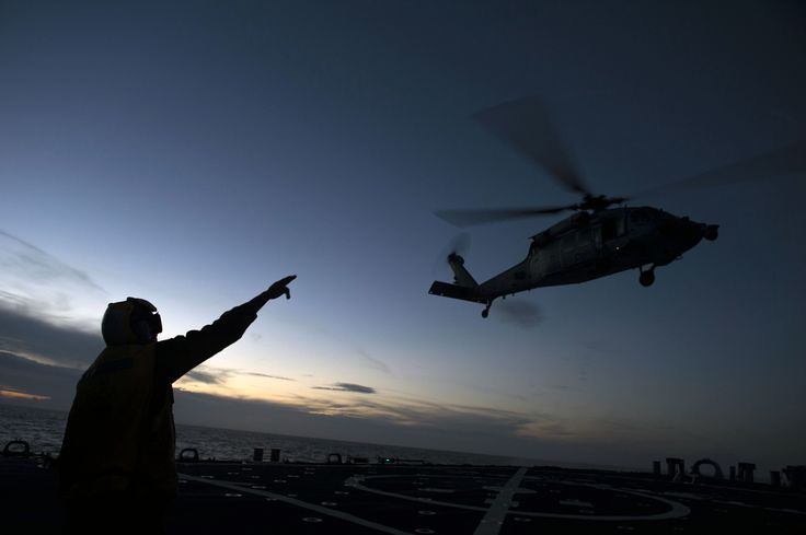 "PHILIPPINE SEA (Sep. 6, 2016) Boatswains Mate 2nd Class Rosben Constant directs a MH-60S Sea Hawk helicopter, assigned to the ""Golden Falcons"" of Helicopter Sea Combat Squadron (HSC) 12, from the flight deck of the Arleigh Burke-class guided-missile destroyer USS Curtis Wilbur (DDG 54) after a refueling. Curtis Wilbur is on patrol with Carrier Strike Group Five (CSG 5) in the Philippine Sea supporting security and stability in the Indo-Asia-Pacific region."
