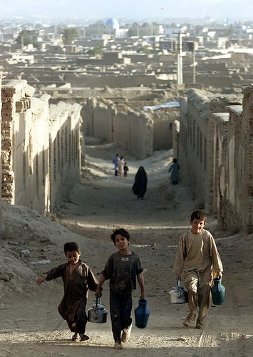 Afghanistan, Kabul. By Justin Heine. Afghan boys carry water, pass through destroyed houses in the west of Kabul. Many houses in Kabul lack running water due to damage caused in the country's long civil war.