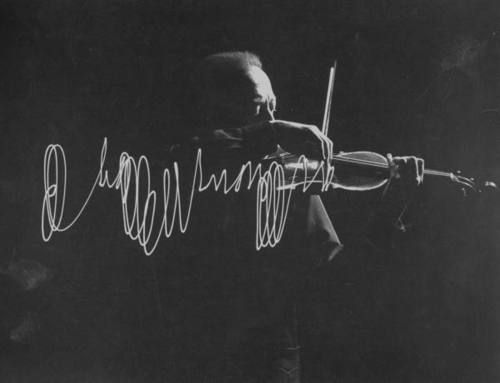 Violinist Jascha Heifetz playing in Mili's darkened studio as light attached to his bow traces the bow movement.