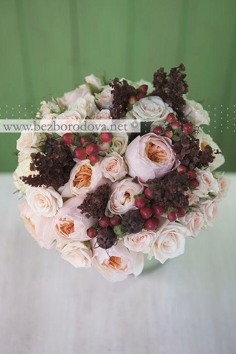 Кремовый свадебный букет из пионовидных роз с красными ягодами и коричневым щавелем.