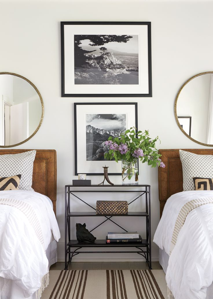 bedroom with twin beds black and white photography and matching mirrors