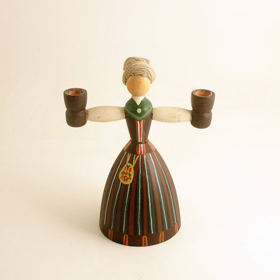 Vintage candleholder. Traditional Swedish candle holder featuring a girl with a candle holder in each hand. Made of painted wood with yarn hair. A wonderful addition to your vintage decor. Candleholder measures approx. 5 1/2 inches tall and 4 1/4 inches wide, at widest point. Base measures approx. 2 3/4 inches in diameter. Some wear and color loss consistent with age. Remnants of wax on the candleholders. Marked Vaster Farnebo marked on bottom. Vaster Farnebo is a municipality in Sweden…