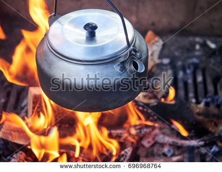 Stock Photo: Metallic coffee pot in campfire heat. Wood burning with flames beneath the pot. -