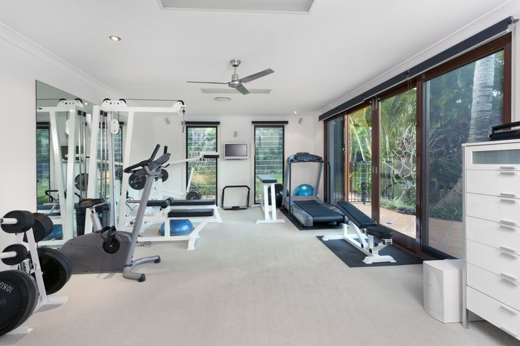 This large, open room has been transformed into a home gym with lots of equipment. Large windows and glass doors show the tropical view.