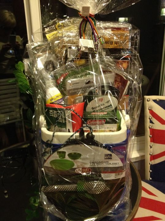 Camping theme gift basket stuffed into a small cooler and tied-up with bungee cords! Cute! Great gift basket idea for men!
