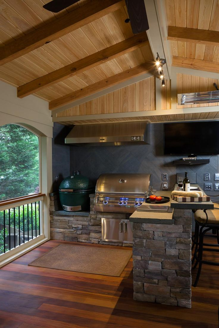 The homeowners now have an outdoor kitchen complete with a built-in gas grill with side burners, a Big Green Egg and a large commercial hood. The porch is designed by Mosaic Group to include a built-in trash receptacle and storage, along with a raised bar with bluestone countertops. The backsplash is tile.