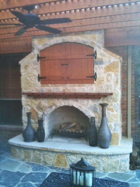 TV Hidden Behind Doors Above Natural Stone Fireplace