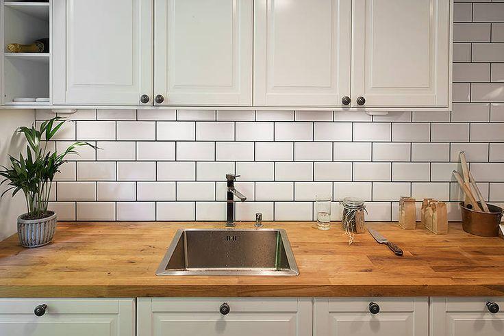 Profilowane fronty szafek, ozdobione uchwytami w stylu retro prezentują się ciekawie na tle wyrazistej struktury cegiełki na ścianie. Podświetlone od dołu wiszące meble rzucają dobre światło na blat roboczy wykonany z drewna. A otwarte półki dodają zabudowie lekkości.