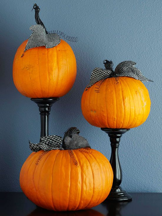 Pumpkins on black candlesticks.
